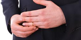man taking wedding ring off finger