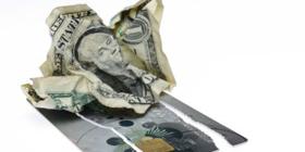 crumpled dollar bill on cut up credit card